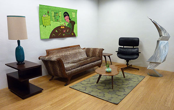 The Vintage Purse quilt hanging over faux leopard sofa and sculpture